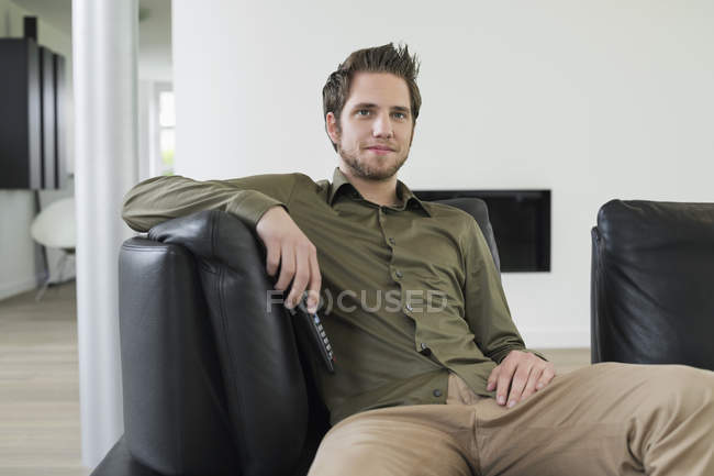 Positive young man watching television on sofa at home — Stock Photo