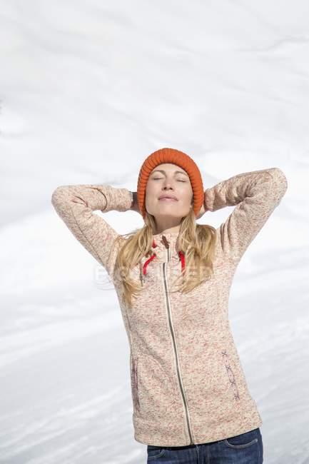 Розслабленої жінка в knit капелюх з очі закриті стоячи в снігу — стокове фото