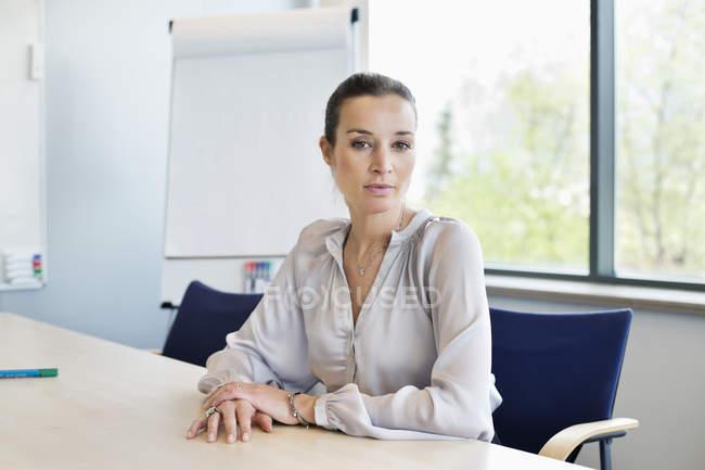 Портрет уверенной деловой женщины, сидящей за столом в офисе — стоковое фото