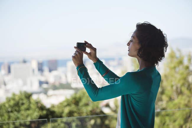 Женщина фотографирует город с помощью мобильного телефона — стоковое фото