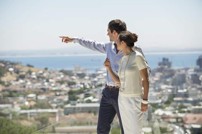 Couple regardant la vue sur la ville depuis la terrasse et pointant — Photo de stock