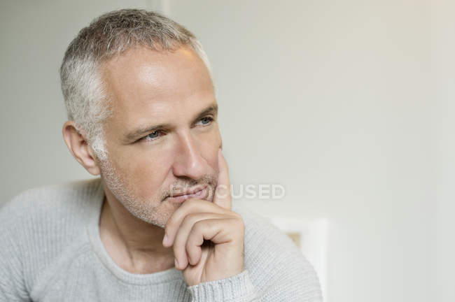 Close-up of thoughtful grey haired man with hand on chin — Stock Photo