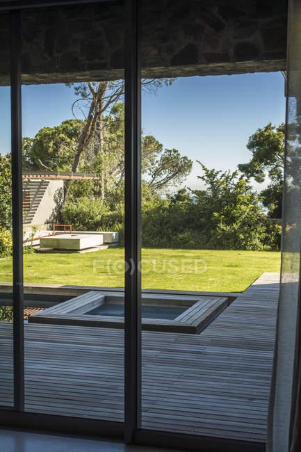 Лаун и горячая туба, вид из стеклянной двери дома в сельской местности — стоковое фото