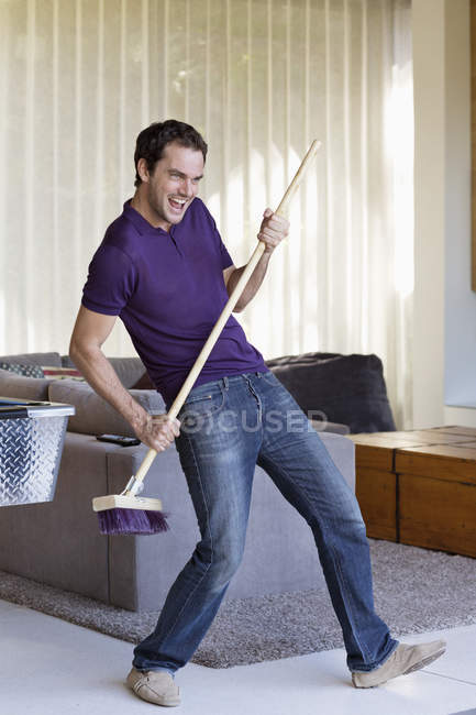 Man holding mop as guitar in living room — Stock Photo