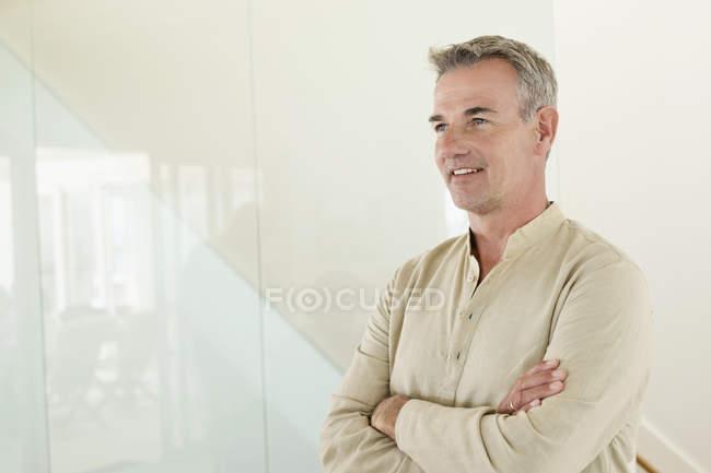 Homme souriant debout avec les bras croisés devant le mur — Photo de stock