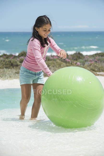 Mädchen spielt mit Fitnessball am Strand — Stockfoto