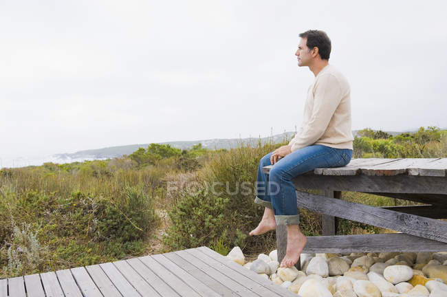Thoughtful man sitting on boardwalk in nature — Stock Photo