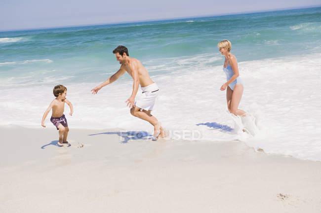 Família alegre jogando na praia arenosa — Fotografia de Stock