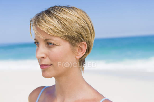 Close-up of blonde woman with short hair thinking on beach — Stock Photo