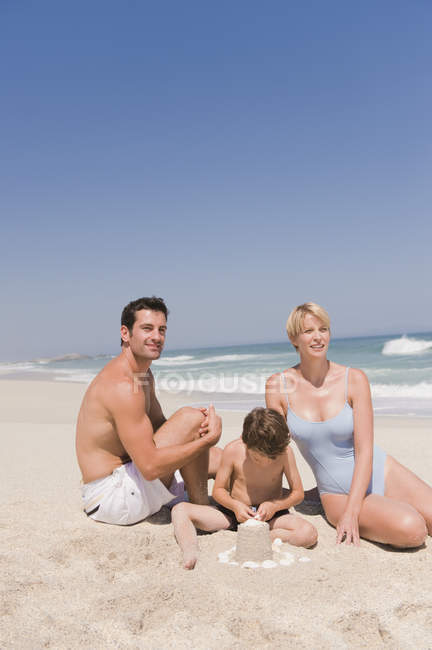 Portrait of happy family on vacations on sandy beach — Stock Photo