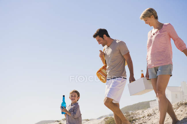 Happy family on vacations walking on beach — Stock Photo