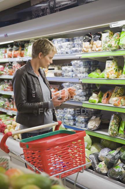 Жінка, покупка упакованих продуктів харчування в супермаркеті — стокове фото