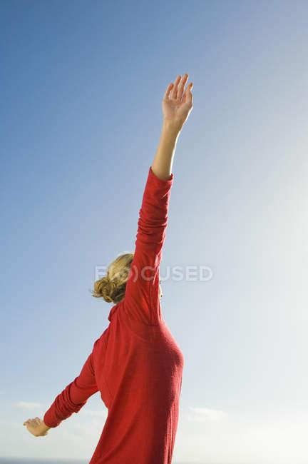 Frau im roten Pullover Strecken Arme gegen blauen Himmel — Stockfoto