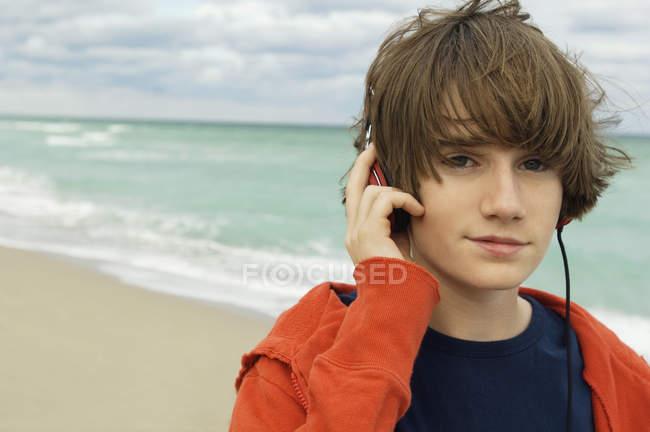 Portrait of boy listening to headphones on beach under cloudy sky — Stock Photo