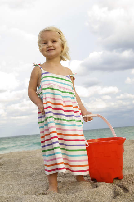 Cute little girl holding sand pail on beach — Stock Photo