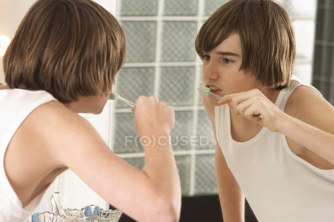 Adolescente ragazzo lavarsi i denti davanti allo specchio in bagno — Foto stock