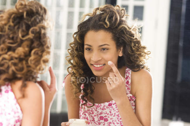 Teenage girl applying moisturizer on face in front of mirror — Stock Photo