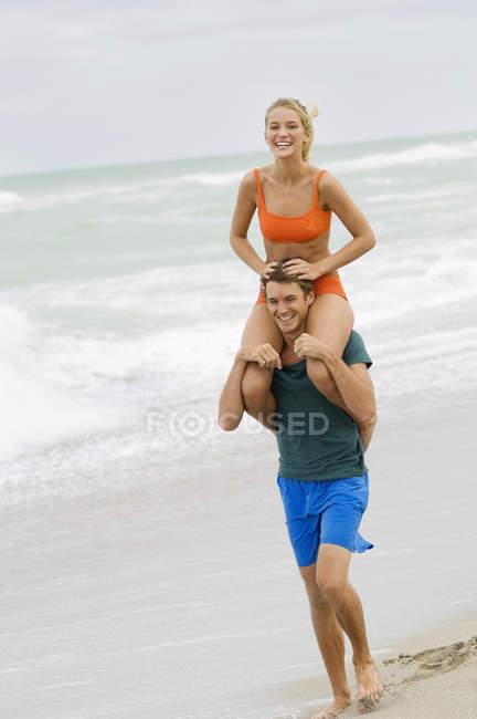 Uomo che trasporta donna sulle spalle sulla spiaggia — Foto stock