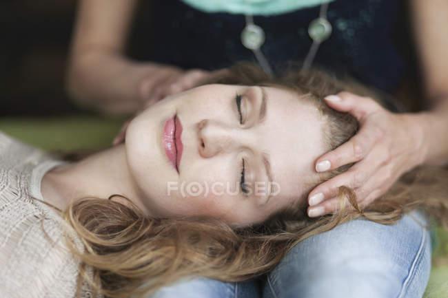 Close-up de mulher relaxada deitada no colo da mãe — Fotografia de Stock