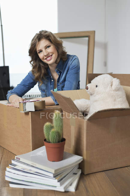 Woman sitting near cardboard boxes in apartment and smiling — Stock Photo