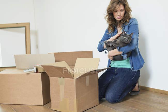 Gato de explotación de mujer en piso cerca de cajas de cartón - foto de stock