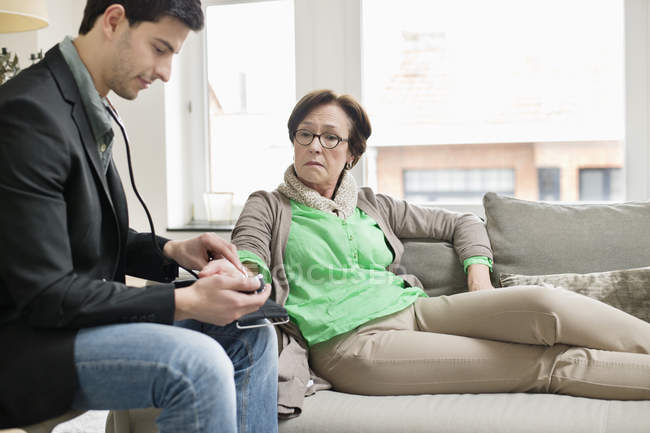Male doctor examining female patient on sofa — Stock Photo