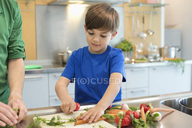 Little boy cutting vegetables in modern kitchen — Stock Photo