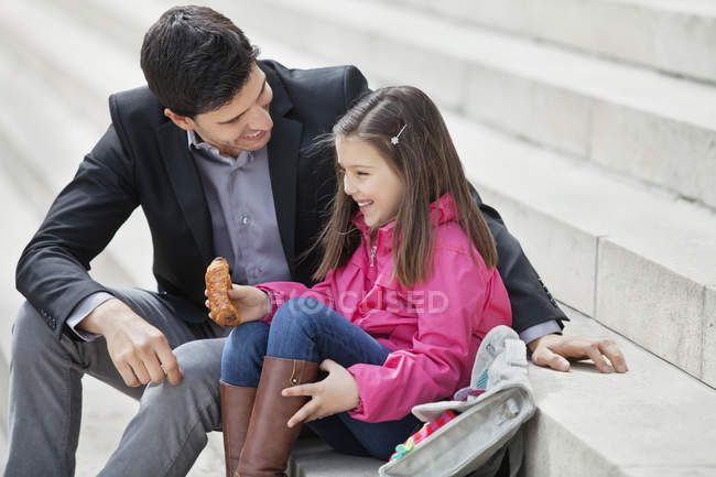 Man sitting on stairs with daughter and eating pain au chocolat — Stock Photo