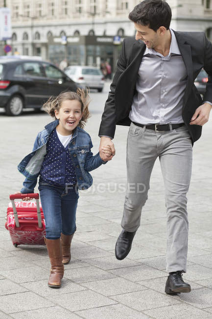 Girl pulling trolley bag while running with father on street — Stock Photo