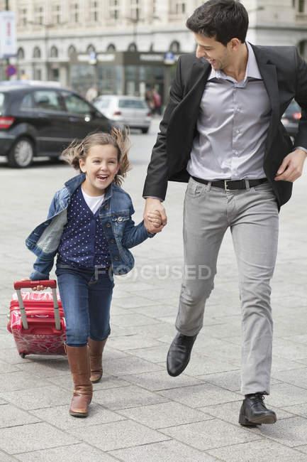 Menina que puxa o saco do trole ao funcionar com o pai na rua — Fotografia de Stock