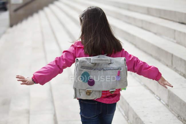 Opinião traseira a menina com a trouxa que anda em etapas — Fotografia de Stock