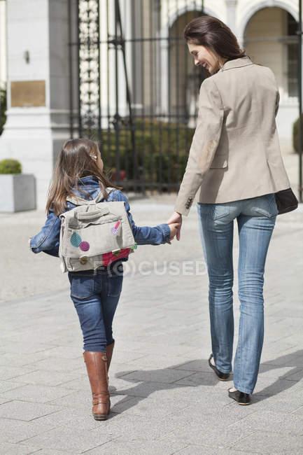 Дівчина з матір'ю ходять до школи тримаючись за руки — стокове фото