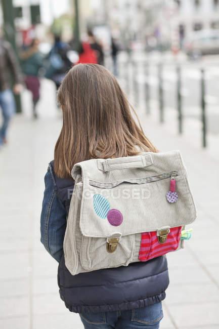 Opinião traseira a menina com a trouxa que anda abaixo da rua — Fotografia de Stock