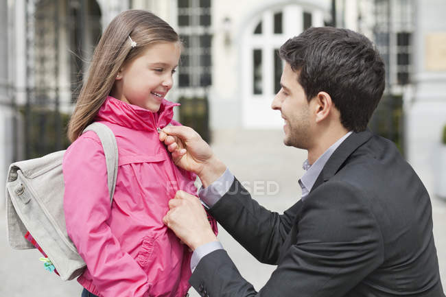 Man talking to daughter and zipping up her jacket on street — Foto stock
