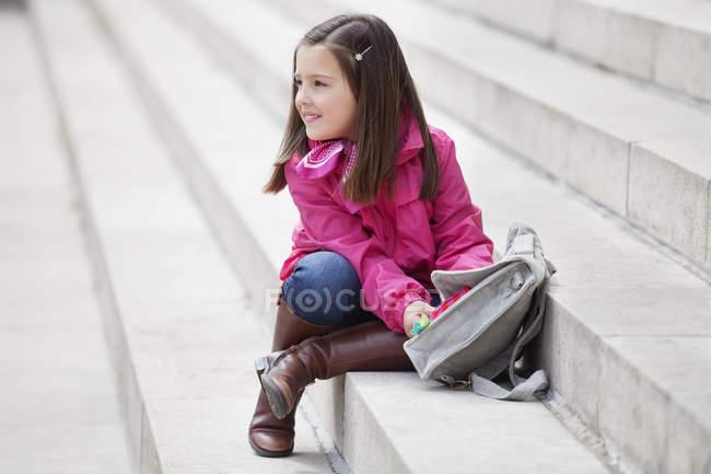 Menina abrindo a mochila na escada ao ar livre — Fotografia de Stock