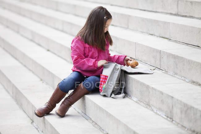 Menina que toma para fora o alimento do schoolbag ao sentar-se em escadas — Fotografia de Stock