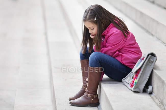 Estudante sonhador pequeno que senta-se em escadas ao ar livre — Fotografia de Stock