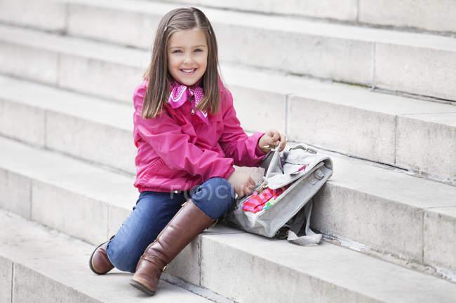 Retrato do schoolbag de sorriso da abertura da menina em escadas ao ar livre — Fotografia de Stock