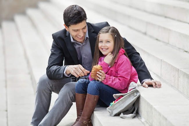 Man sitting on stairs with daughter and eating pain au chocolat — Foto stock
