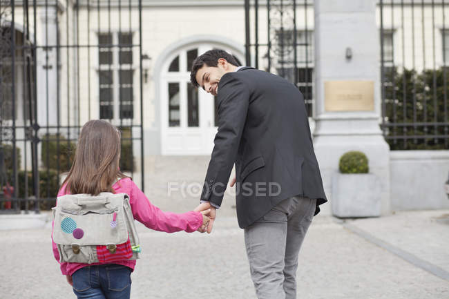 Girl walking towards school with father — Foto stock