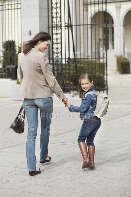 Happy girl with mother walking to school — Stock Photo