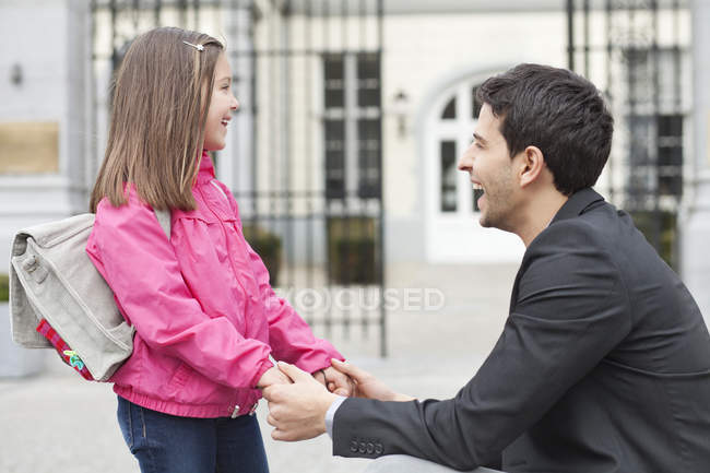 Laughing man talking to daughter, holding hands — стоковое фото