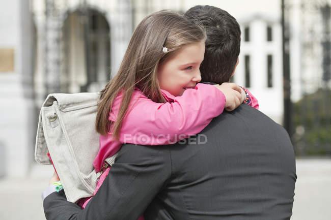 Süße Mädchen umarmen Vater im Freien — Stockfoto