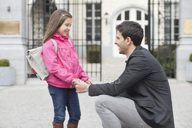 Laughing man talking to daughter, holding hands — Foto stock