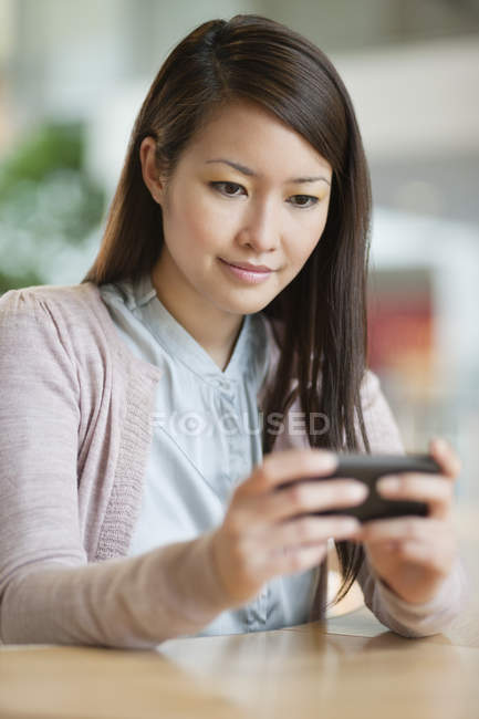 Businesswoman text messaging on mobile phone in office — Stock Photo