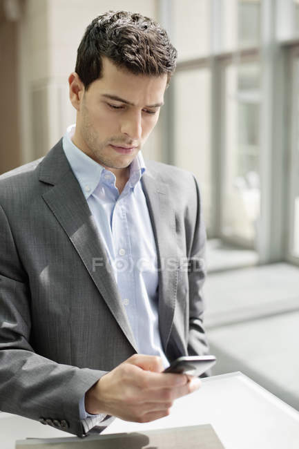 Close-up of young confident businessman text messaging — Stock Photo