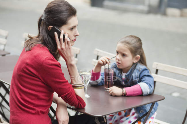 Жінка з маленькою дочкою сидить в кафе і розмовляє по телефону — стокове фото