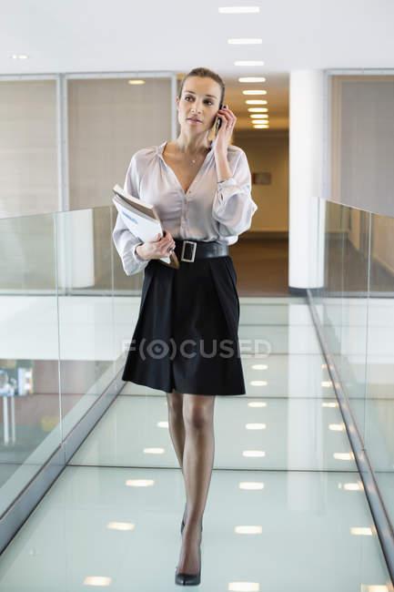 Деловая женщина разговаривает по мобильному телефону во время прогулки по офисному коридору — стоковое фото