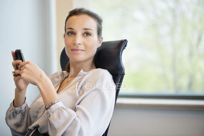 Ritratto di donna di affari che messaggi di testo con cellulare in ufficio — Foto stock