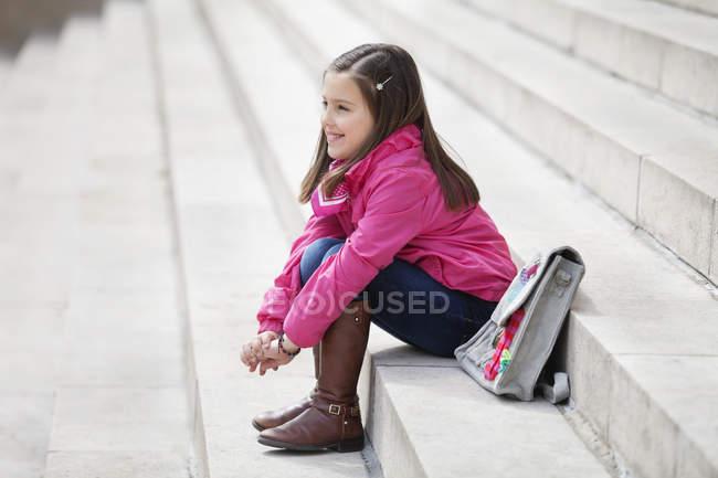 Menina com o schoolbag que senta-se em escadas ao ar livre — Fotografia de Stock